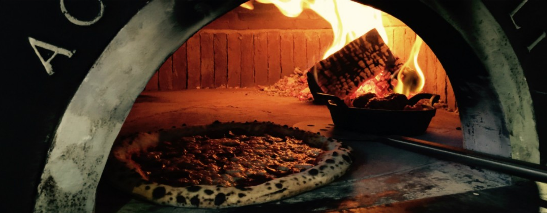 pizza getting cooked in coal
